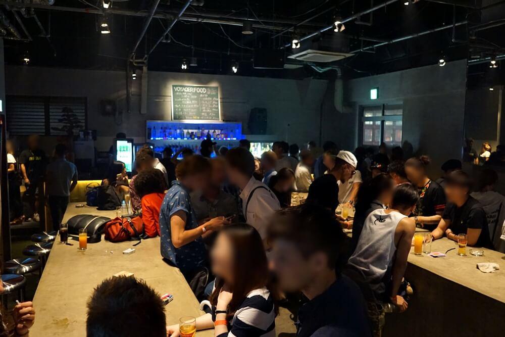 これがボイジャースタンド大阪の全体像。長~いテーブルが二つあり、それをみんで囲って飲んでいる。